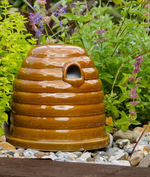 A ceramic bee and small mammal nester shown in the garden