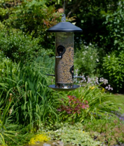 A seed feeder for garden birds is hanging in the garden